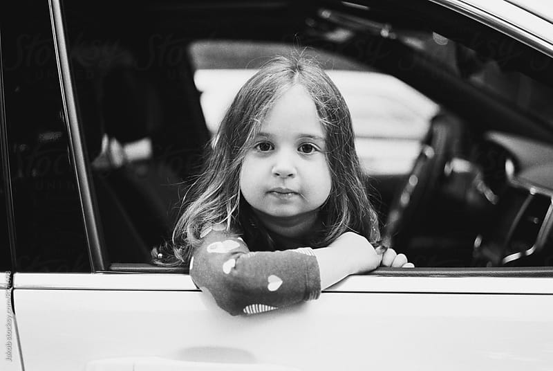Cute young girl looking out the window of a car by Jakob for Stocksy United