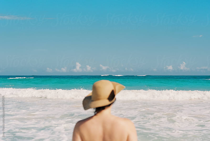 Woman in soft focus looks out across the ocean in the Caribbean by Joey Pasco for Stocksy United