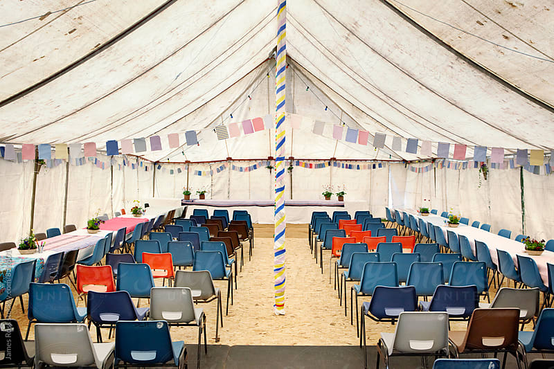 An empty marquee with lines of chairs by James Ross for Stocksy United