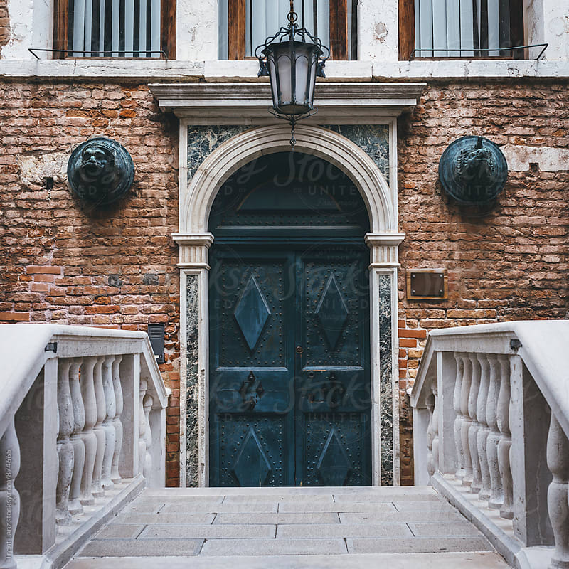 Brick facade with decorated door and sculptures in Venice by Trent Lanz for Stocksy United
