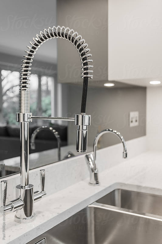 Modern chrome sprung mixer tap in contemporary kitchen. by Paul Phillips for Stocksy United