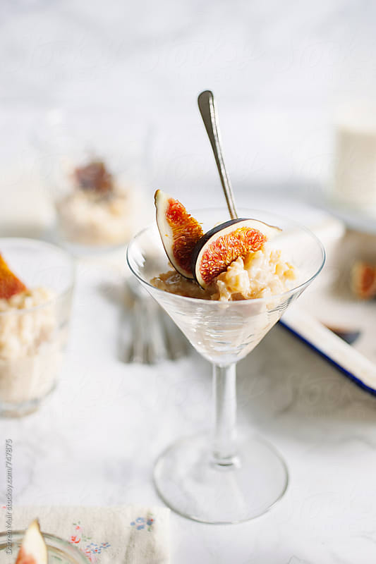 Sweet rice pudding with figs served in a glass with a spoon. by Darren Muir for Stocksy United