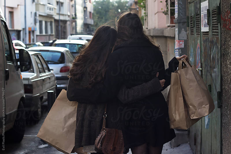 Two female friends huging each other from back by Branislava Živić for Stocksy United