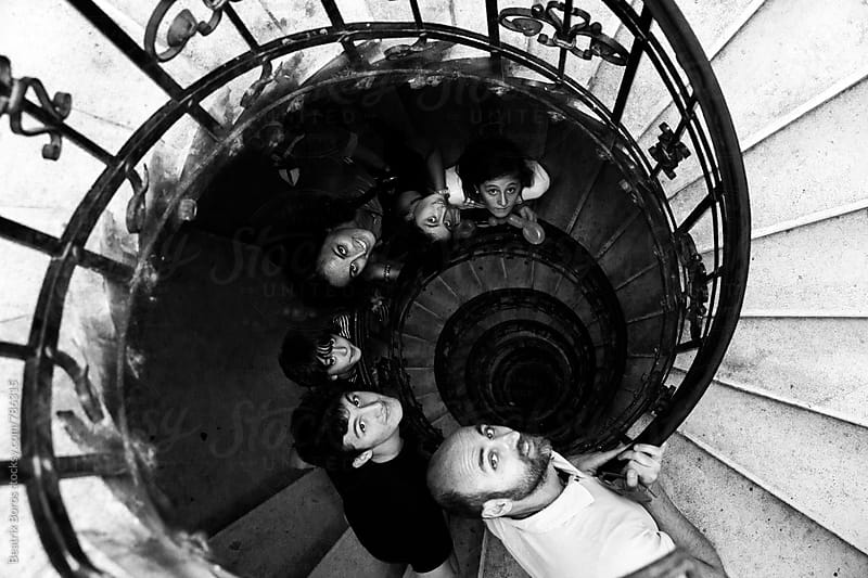 Family with 4 kids looking up at camera on a spiral staircase by Beatrix Boros for Stocksy United