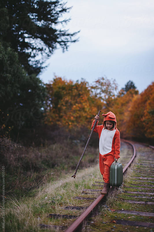 Child in fox costume walking with suitcase along train tracks by Rob and Julia Campbell for Stocksy United