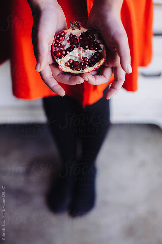 Girl in Red Dress Holding a Pomegranate  by Gabrielle Lutze for Stocksy United