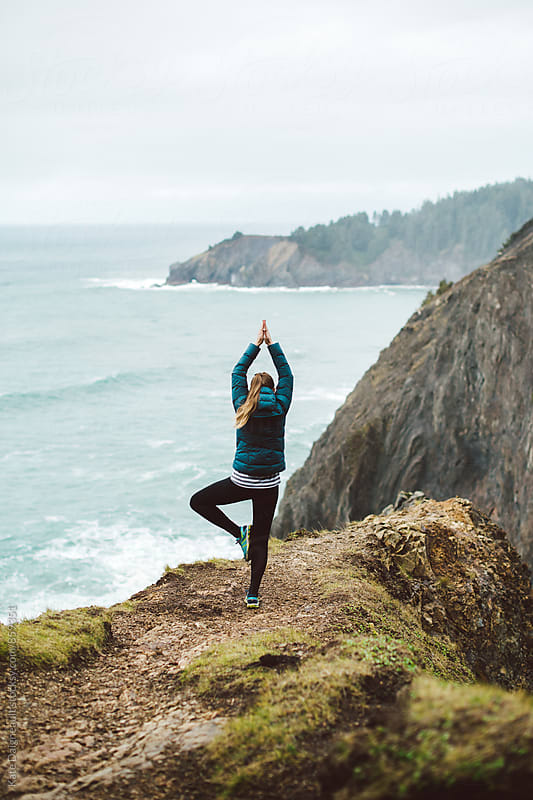 Young woman doing a yoga pose on the edge of a very steep cliff looking out over the ocean. by Kate Daigneault for Stocksy United