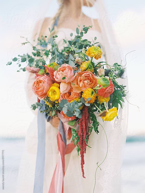 bright spring time flowers for wedding wtih bride on beach by wendy laurel for Stocksy United