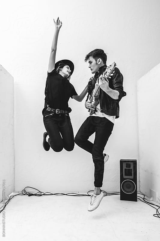 Rockers couple jumping with their electric guitar in recording studio. by BONNINSTUDIO for Stocksy United