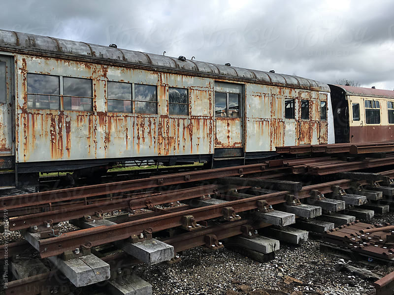 Rusting railway carriages and track. by Paul Phillips for Stocksy United