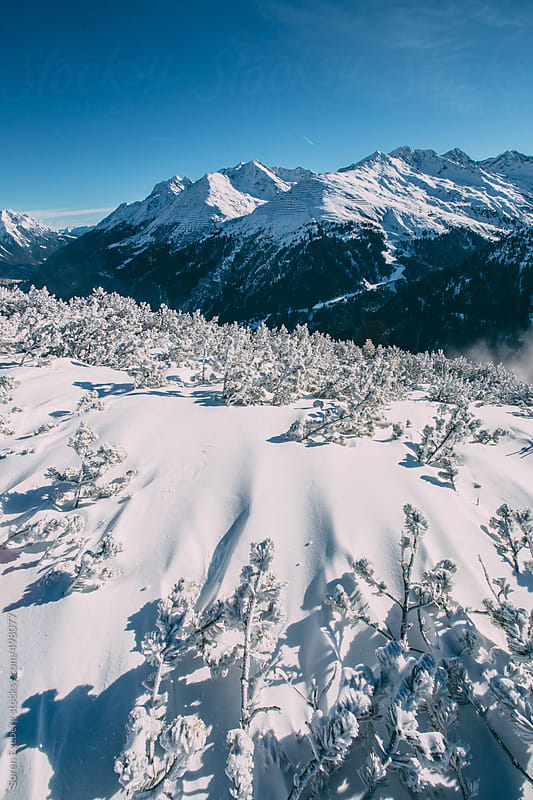 Snow covered mountain landscape in winter with peaks in the distance by Soren Egeberg for Stocksy United