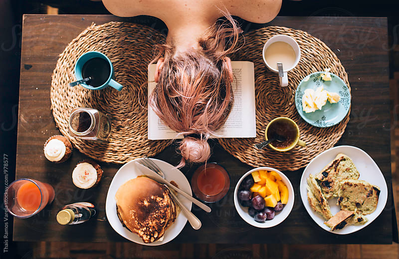 woman over a breakfast table by Thais Ramos Varela for Stocksy United
