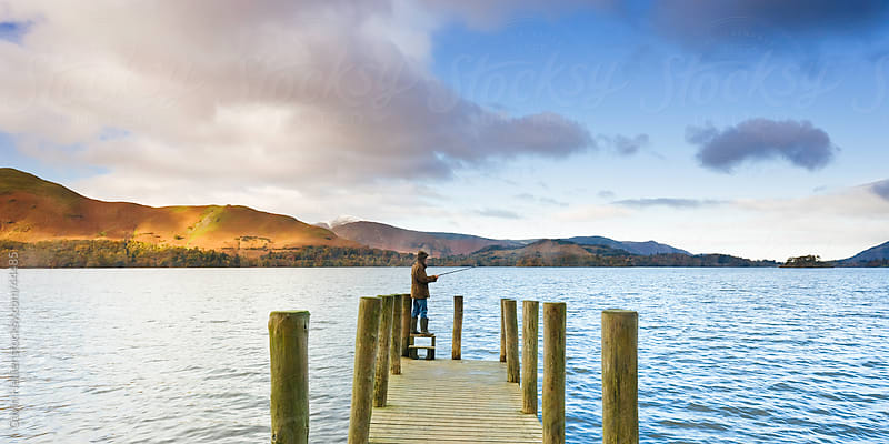 Derwent Water, Lake District National Park, Cumbria, England, UK  - Fisherman on the  wooden jetty at Barrow Bay landing by Gavin Hellier for Stocksy United