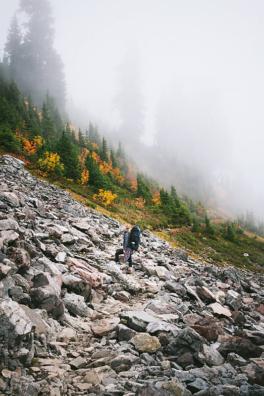 Young Female Backpacker Standing In Boulder Field Near Foggy Subalpine Forest by Luke Mattson for Stocksy United