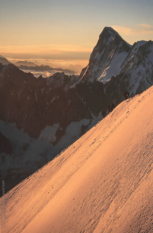 Mountain scenery with climbers descending snow ridge at sunrise by Søren Egeberg Photography for Stocksy United