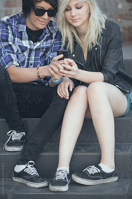 Teenage Couple With a Mobile Phone by Lumina for Stocksy United