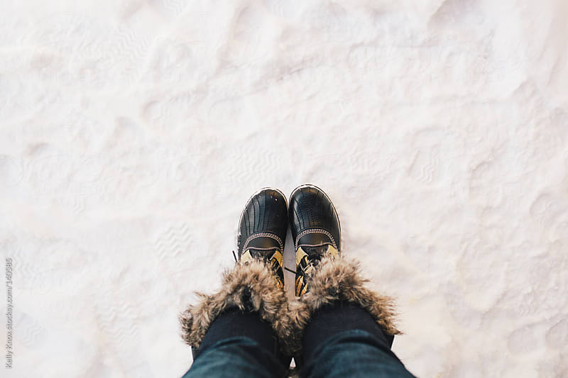 woman looking down at her boots in the snow by Kelly Knox for Stocksy United