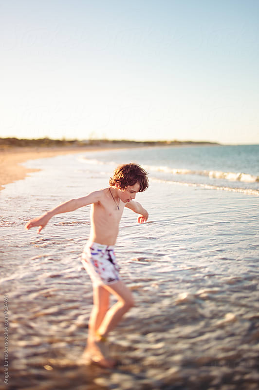 Boy in a bathing suit playing in low waves at the beach at sunset by Angela Lumsden for Stocksy United