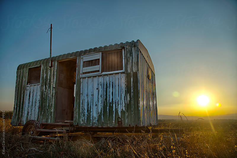 Trailer Wreck in Countryside Field at Sunset by Eldad Carin for Stocksy United