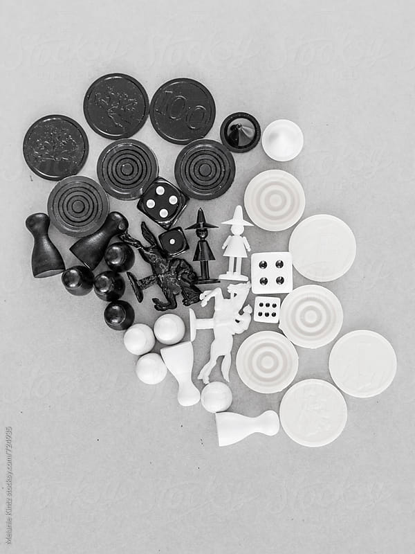 Black and white game pieces on grey background by Melanie Kintz for Stocksy United