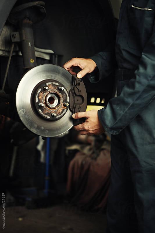 Mechanic fixing brakes. by kkgas for Stocksy United