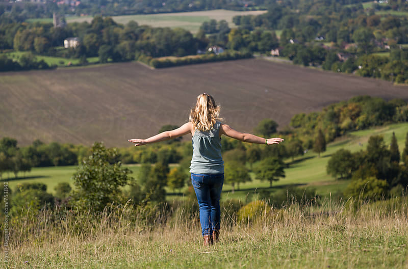 Young girl walking down a hill with arms outspread by Kirsty Begg for Stocksy United