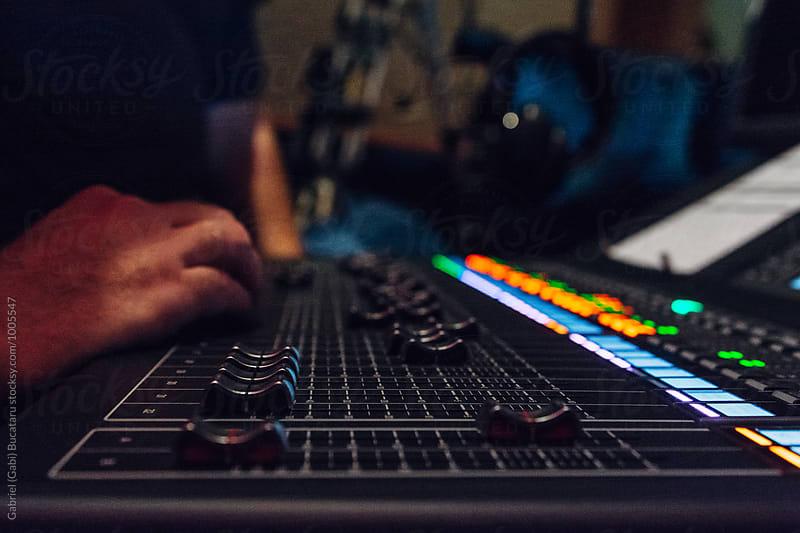 Hands of a sound engineer on a mixing board by Gabriel (Gabi) Bucataru for Stocksy United