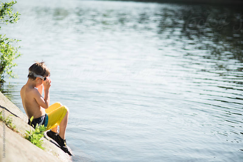 little boy sitting by a lake by Léa Jones for Stocksy United