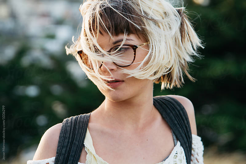 close portrait of young female woman girl wearing glasses with hair blown in city park by Jesse Morrow for Stocksy United