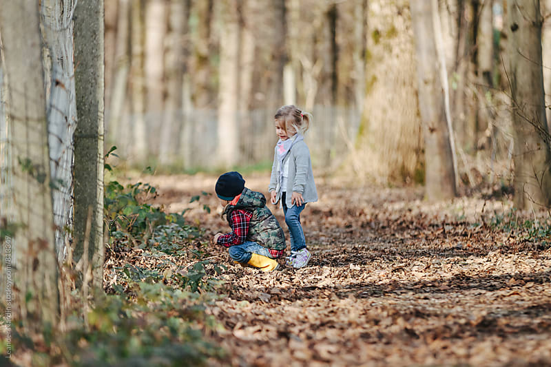 little boy and girl playing outdoors in a forest by Leander Nardin for Stocksy United