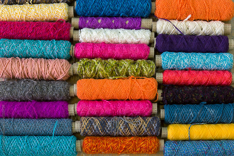 Spindles with different coloured yarn covering the frame by Paul Phillips for Stocksy United