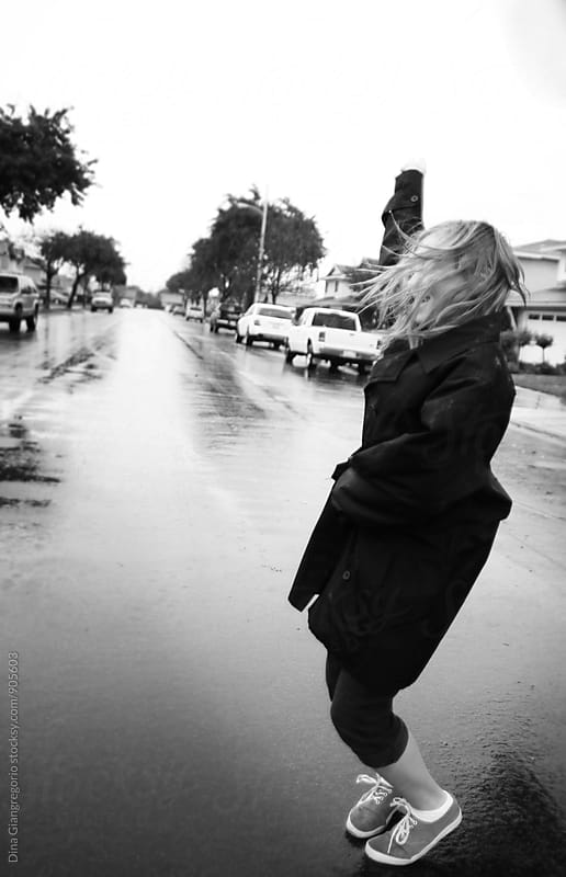 Girl In Street Playing in Rain by Dina Giangregorio for Stocksy United