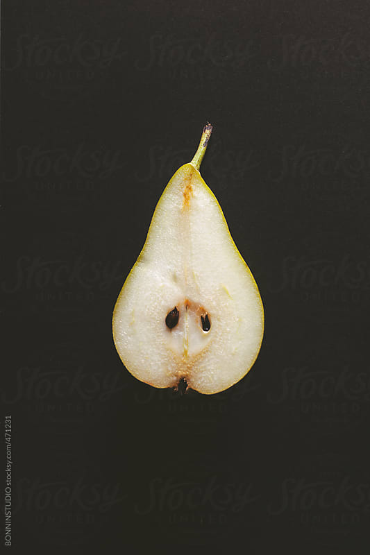 Overhead of sliced pear on black background. by BONNINSTUDIO for Stocksy United