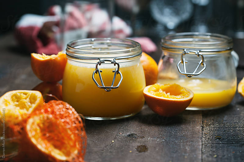 Homemade Seville orange curd,surrounded by squeezed half oranges. by Darren Muir for Stocksy United