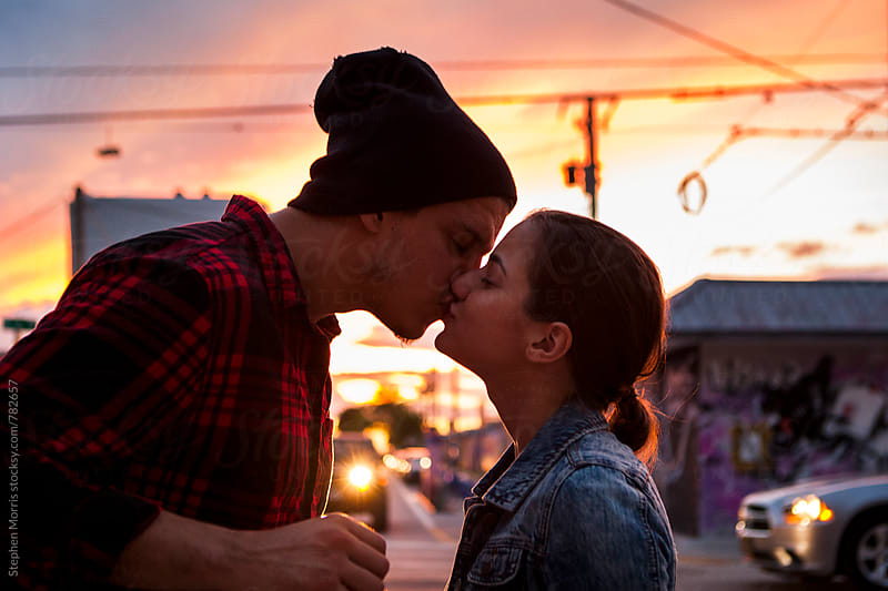 Couple kissing on Street at Sunset by Stephen Morris for Stocksy United