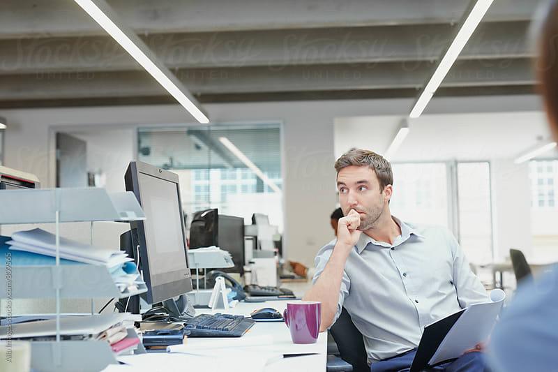 Concerned businessman multitasking leaning over desk observing share price by Aila Images for Stocksy United