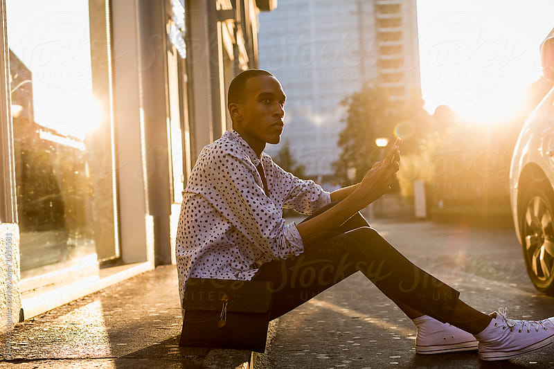 Stylish African American Businessman using mobile phone outdoor in the City by Mauro Grigollo for Stocksy United