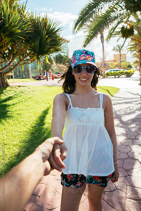 Happy woman in cap and sunglasses holding man's hand by Alejandro Moreno de Carlos for Stocksy United