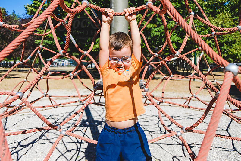 Happy Male Toddler Climbing a Net at the Playground by Giorgio Magini for Stocksy United
