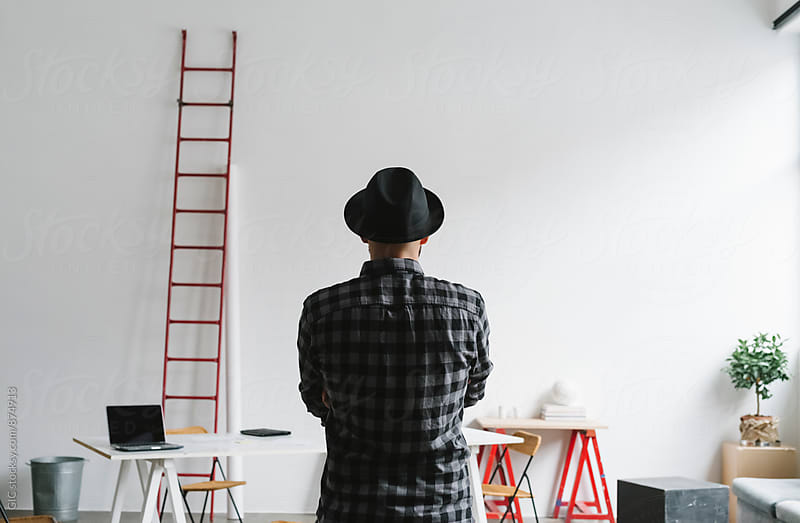 Man with hat in the office by WAVE for Stocksy United