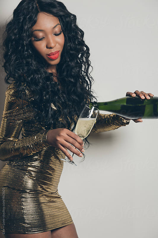 Black woman posing while pouring champagne into a glass by Lior + Lone for Stocksy United