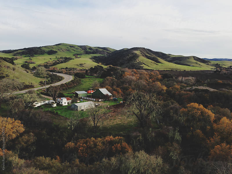 Farm Under Green Hills by Kevin Russ for Stocksy United