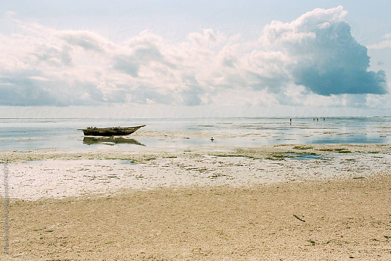 Traditional wooden dhow moored at low tide in Zanzibar by Helen Rushbrook for Stocksy United