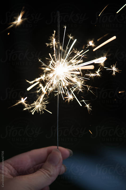 Woman's hand holding sparkler on the 4th of July by Cara Dolan for Stocksy United