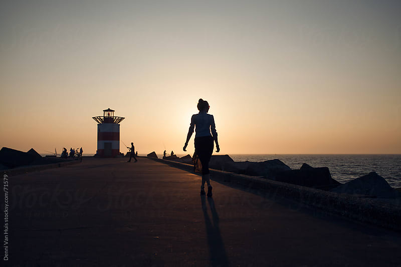 Woman walking on a harbour jetties overlooking the ocean during sunset by Denni Van Huis for Stocksy United