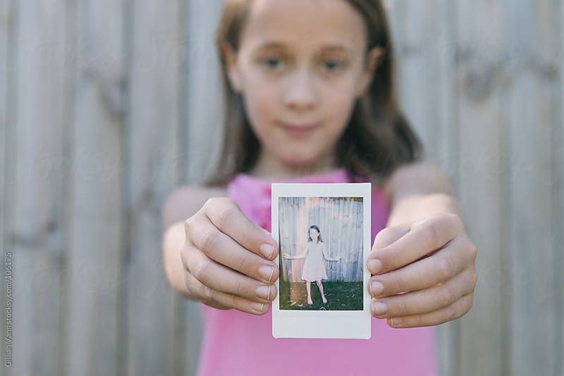 little girl with polaroid photo of herself by Gillian Vann for Stocksy United