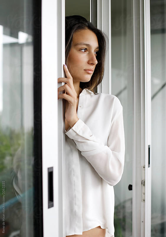 young woman in white shirt in between sliding doors by Rene de Haan for Stocksy United