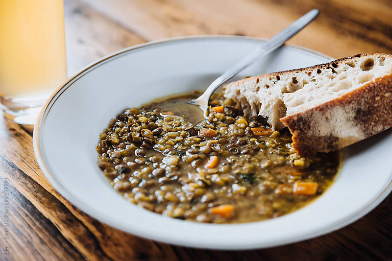 Lentil and carrot soup with bread by Lior + Lone for Stocksy United
