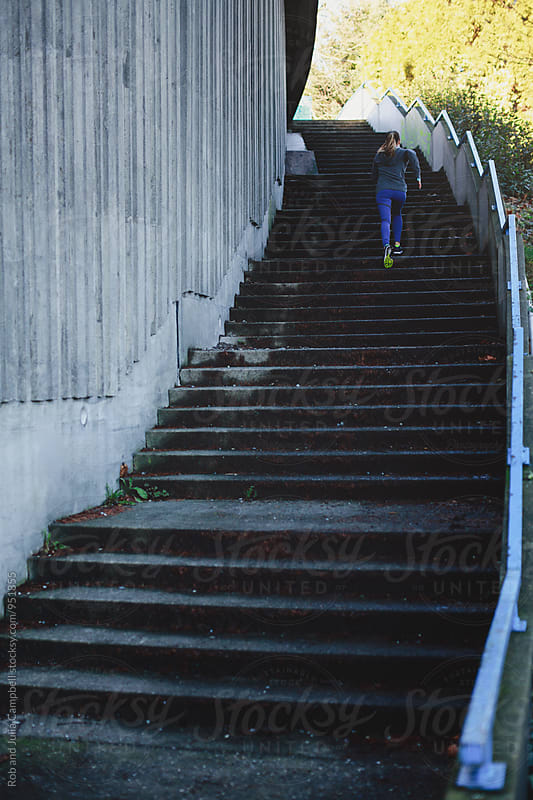 Young caucasian woman running up stairs outside in urban city by Rob and Julia Campbell for Stocksy United
