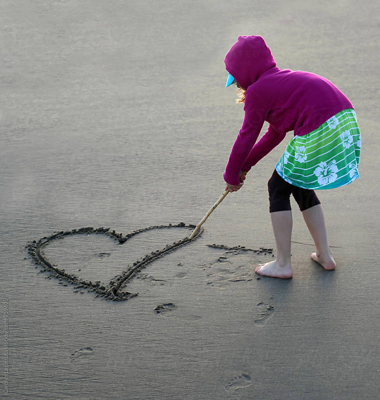 Little girl carving a heart in the sand with a stick by Carolyn Lagattuta for Stocksy United